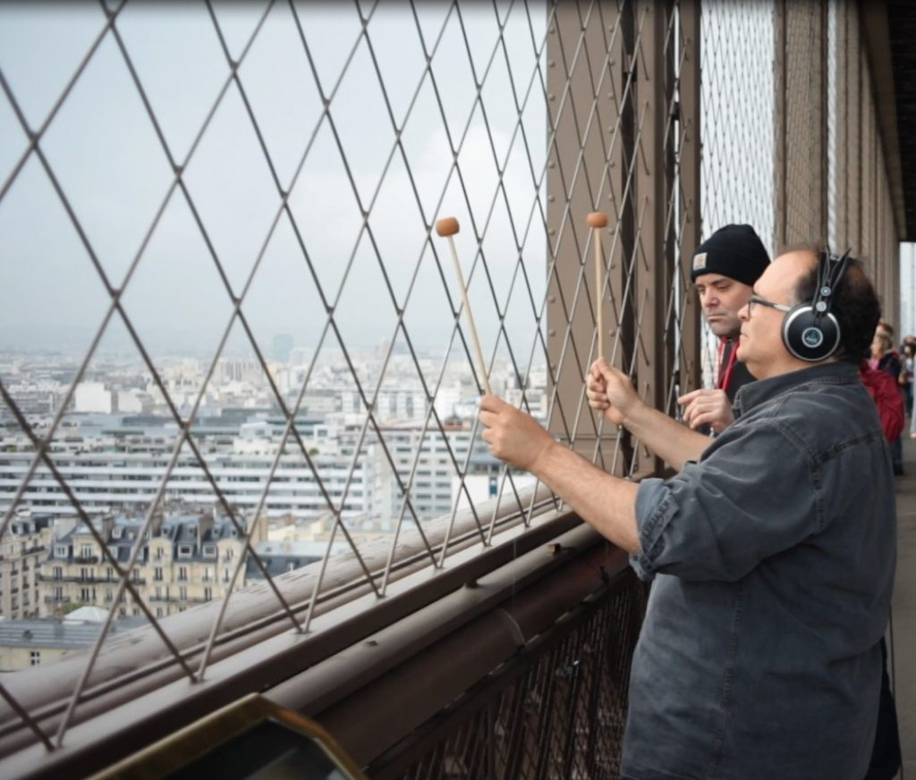 COMPOSER JOSEPH BERTOLOZZI AT FENCE WITH MALLETS AT THE EIFFEL TOWER, Image c. 2013, Blue Wings Press